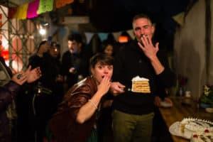 La marié et le mariés posent avec un morceau de gâteau